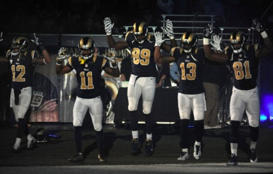 Members of the St. Louis Rams raise their arms as they walk onto the field during introductions before an NFL football game against the Oakland Raiders, Sunday, Nov. 30, 2014, in St. Louis. (Image source: AP/L.G. Patterson)